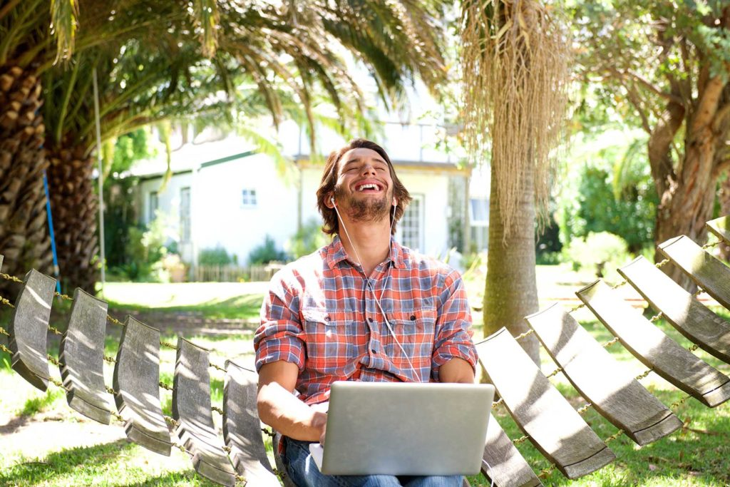 young man laughing with laptop outdoors p6hh77j